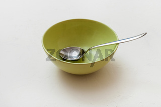 green bowl with spoon on white plaster