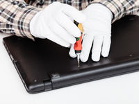 serviceman disassembles laptop with screwdriver