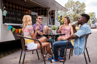 friends with drinks sitting at table at food truck