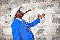 Havana, Cuba - December 12, 2016:  Traditional Cuban man posing for photos while smoking big cuban cigar in Old Havana, Cuba.