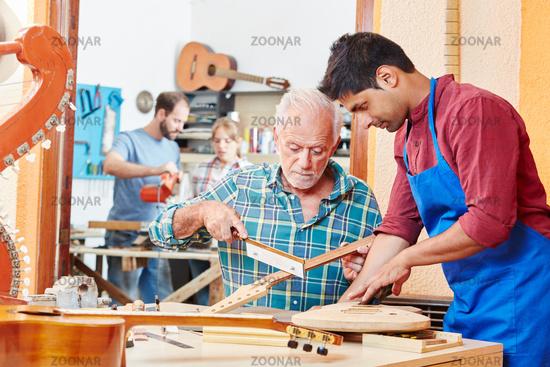 Handwerker zeigt Lehrling die Arbeit
