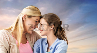 happy smiling mother and daughter over sky