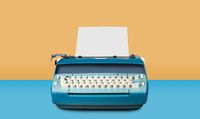 Old electric typewriter on blue table background