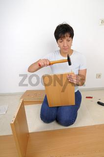 Regal zusammenbauen - Woman assembling furniture