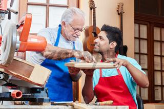 Alter Handwerker bildet Azubi aus