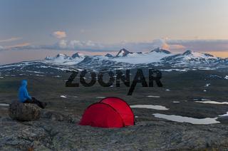 Wanderer blickt von seinem Zelt aus zum Sulitelmamassiv mit dem Sulitelmagletscher, Welterbe Laponia, Lappland, Schweden, und dem Gipfel Suliskongen, Provinz Nordland, Norwegen