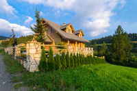 Traditional wooden mountain house built from wood logs on summer sunny day