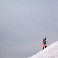 Skier before downhill on snowy slope for freeriding and overcast misty sky