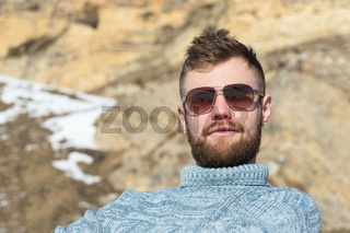 Portrait of a traveler hipster in sunglasses and a knitted gray sweater resting on nature at winter