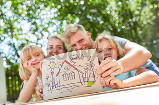 Familie zeigt bunte Zeichnung mit Eigenheim
