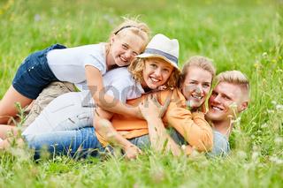 Familie und Kinder kuscheln zusammen im Gras