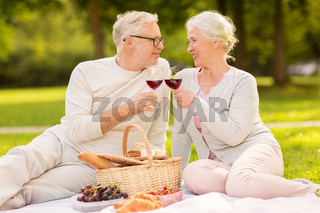 happy senior couple having picnic at summer park