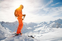 A skier in an orange overall with a backpack on his back wearing a helmet and with ski poles in his hands is standing on a precipice in front of a snowy abyss in the background of a beautiful Caucasian mountain landscape