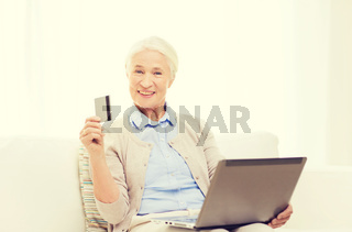 senior woman with laptop and credit card at home