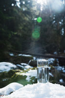 A transparent glass glass with drinking mountain water stands in the snow against a background of a clean frost mountain river in winter. The concept of drinking mountain drinking mineral water and the production of mineral environmentally friendly drinki