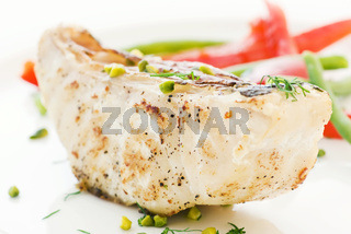 Parrot fish steak with vegetables as closeup on a white plate