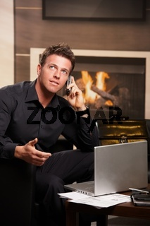 Businessman talking on mobile at home
