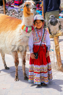 Local girl in traditional dress standing at the market in Maca village in Colca Canyon, Peru