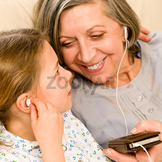Grandmother and young girl listen music together