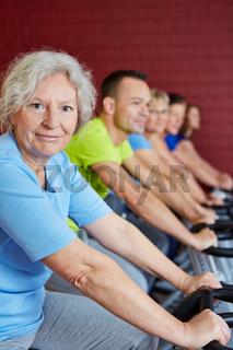 Seniorin beim Spinningkurs im Fitnesscenter