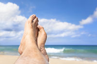relaxed foot lying on the beach