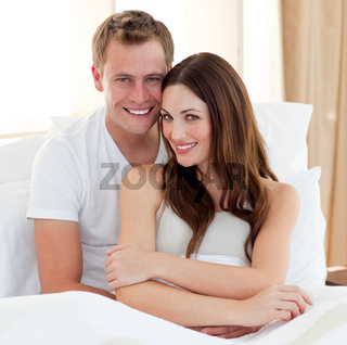 Intimate lovers embracing lying in bed