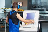 worker operating cnc punch press