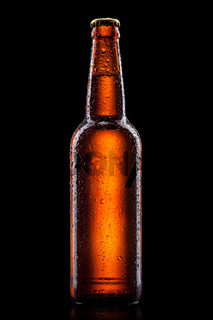 Beer bottle with water drops isolated on black