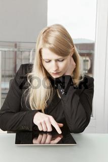 Geschäftsfrau sitzt mit Tablet PC am Tisch