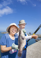 happy senior couple fishing and showing big grouper fish