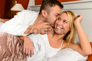 Happy couple bed man giving kiss woman
