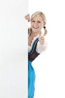 Junge bayerische Frau im Dirndl zeigt Daumen u. hält leere Werbetafel