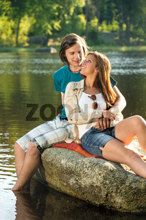 Smiling couple sitting on a rock romantic