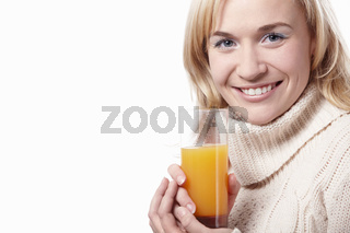 A woman in a sweater with a glass of juice on a white background
