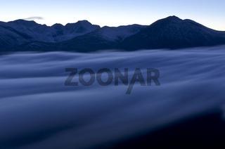 Blick ueber das nebelverhuellte Tal Atndalen zum Gipfel Rondslottet im Rondane Nationalpark, Hedmark