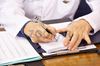 Hände einer Ärztin mit Stift beim Schreiben