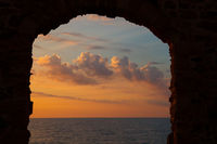 Stone arch, Mediterranean sea and evening sky