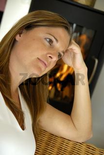Schwangere Frau vor einem Holzofen