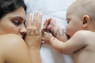 Baby sleeping close to her mother, holding her finger