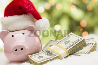 Pink Piggy Bank Wearing Santa Hat Near Stacks of Money on Snowflakes
