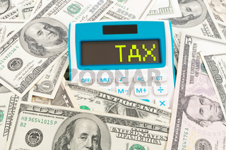 Tax concept, word on calulator with American notes