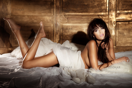 Sensual brunette beauty lying in white bed