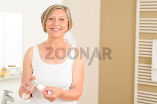 Senior woman smiling in bathroom morning hygiene