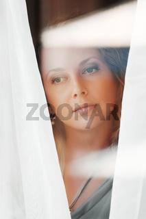 Beautiful woman looking through a window