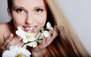 Beautiful blond girl with orchid flower in studio
