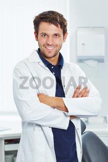 Lächelnder Zahnarzt mit verschränkten Armen