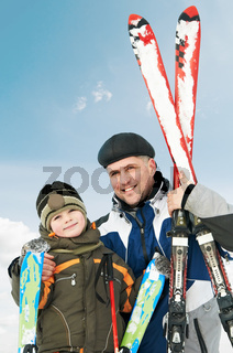 Smiling son and father with skis at winter