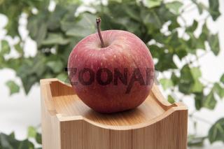 Roter Apfel auf Kiste und mit Efeu