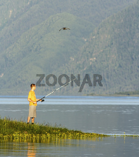 The fisherman fishes on the bank of the beautiful lake in Siberia