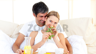 Caucasian couple having breakfast lying in the bed
